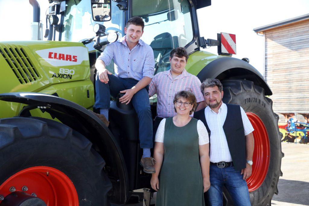 Familie Heindl bei einem CLAAS Traktor