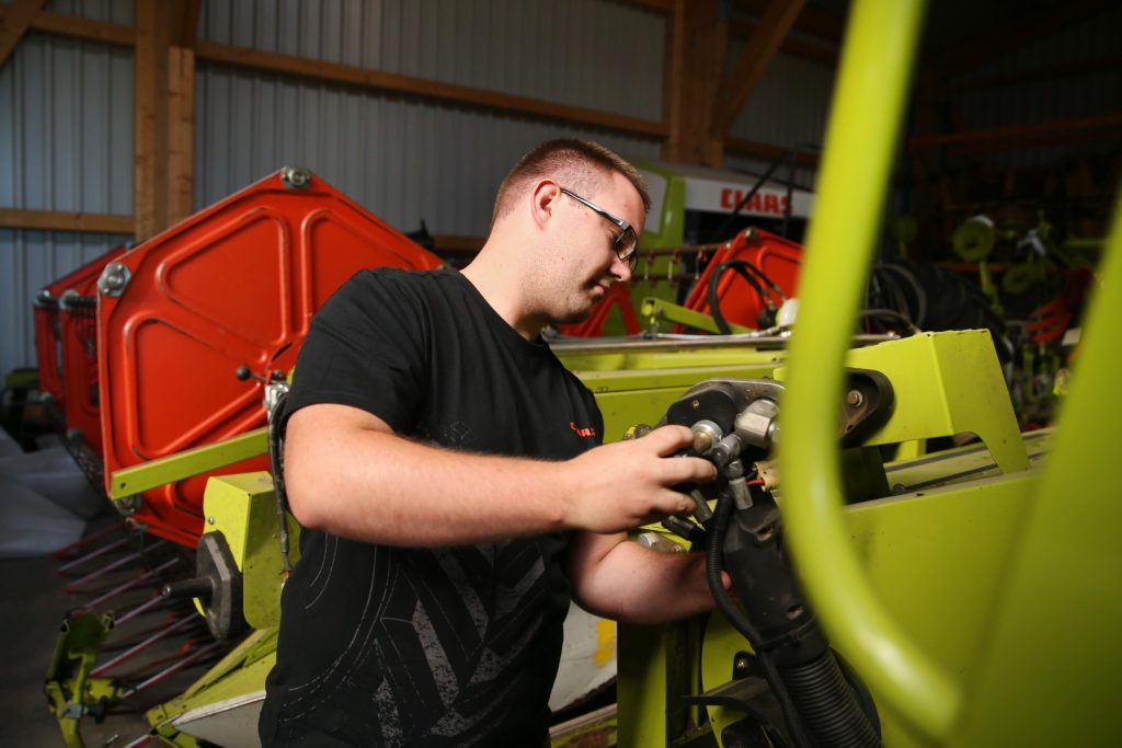Servicetechniker arbeitet an einem CLAAS Mähdrescher